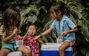 Two young girls and a toddler enjoying shaved ice.