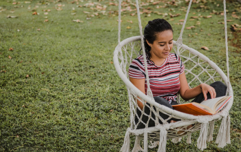 A girl reading a book in a macrame swing